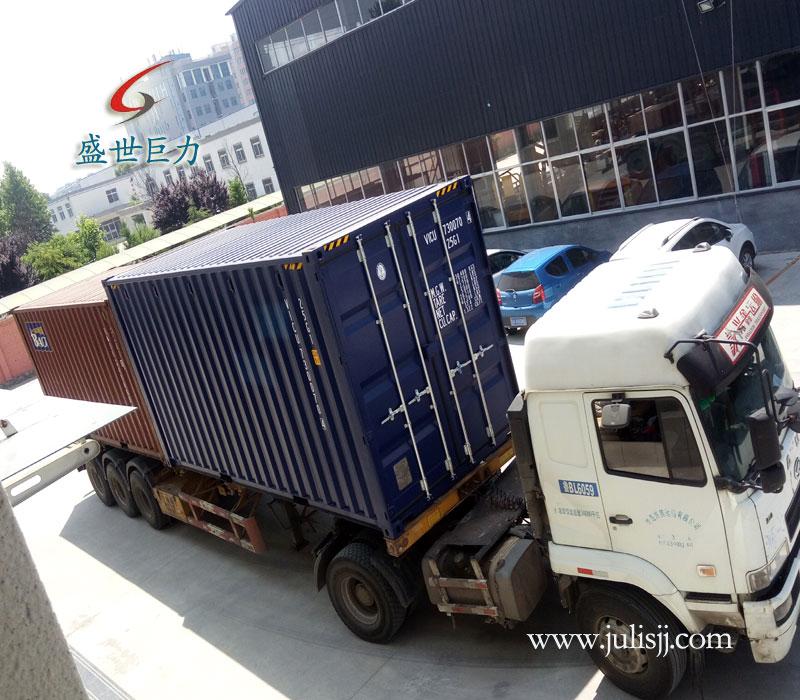 即将装载液压升降平台的集装箱货车